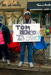 17 Feb 2015. New Orleans, Louisiana.<br /> Early morning Mardi Gras Day. A man holds a sign proclaiming Tom Benson is Sane on St Charles Avenue before the big parades start to roll. Benson is the owner of the NFL New Orleans Saints and the NBA New Orleans Pelicans.<br /> Photo; Charlie Varley/varleypix.com