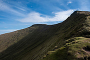 The mountain ridge between Pen Y Fan and Fan Fawr in Brecon Beacons National Park, Wales, Powys, United Kingdom. Pen Y Fan is the highest point in the Brecon Beacons hill and mountain range in South Wales. The National Park was established in 1957 due to the spectacular landscape which is rich in natural beauty.