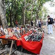Tourists shopping at market stalls selling local souvenirs and handicrafts to tourists visiting Chichen Itza Mayan ruins archeological site in Mexico.