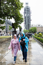 London, UK. 19 July, 2019. Tourists wearing rain ponchos brave heavy rain close to the Houses of Parliament in Westminster.