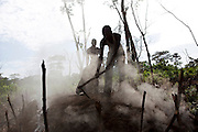 Men work on a makeshift kiln that produces charcoal out of rainforest wood near Bikoro, DRC, May 16, 2009. ©Daniel Beltra