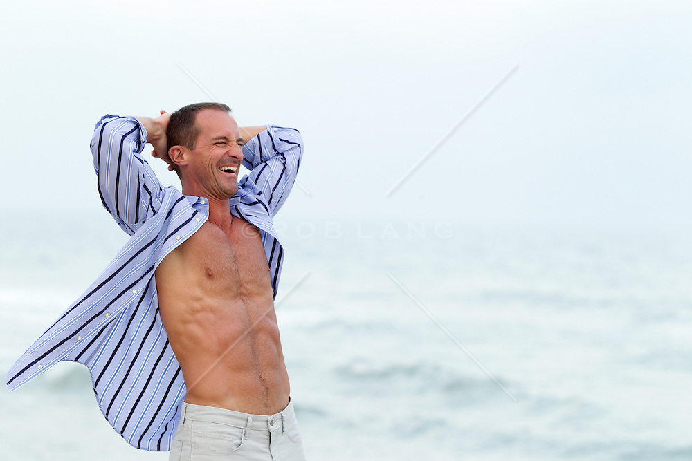 man enjoying the air of the ocean while his shirt blows open in the wind
