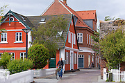 Woman cycling past traditional thatched cottage houses on Fano Island - Fanoe - South Jutland, Denmark