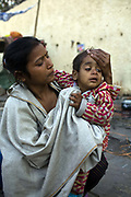 A homless woman cleans her child by the side of the road at a temporary shelter in Karol Bagh, New Delhi, India..