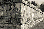 Black and white photo of a Tzompantli or Skull Platform in Chichen Itza, a large pre-Columbian city built by the Maya others show a scene with a human sacrifice; eagles eating all human hearts; and skeletonized warriors with arrows and shields.