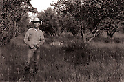 A cowboy stands in a field with his hands in his pockets