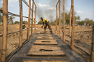 Deng Chol, 30, helps to build latrines for residents of a displacement camp along the banks of the Nile River, in Ahou, South Sudan in Lake State. Hygiene is critical to minimizing the spread of disease in the camps. An estimated 716,100 have been displaced in South Sudan with an additional 166,900 fleeing to neighboring countries as a result of conflict that erupted in mid-December 2013. Catholic Relief Services and Caritas Internationalis have been responding with latrines, hand washing stations, and emergency shelter kits and non food items such as kitchen materials and hygiene materials.