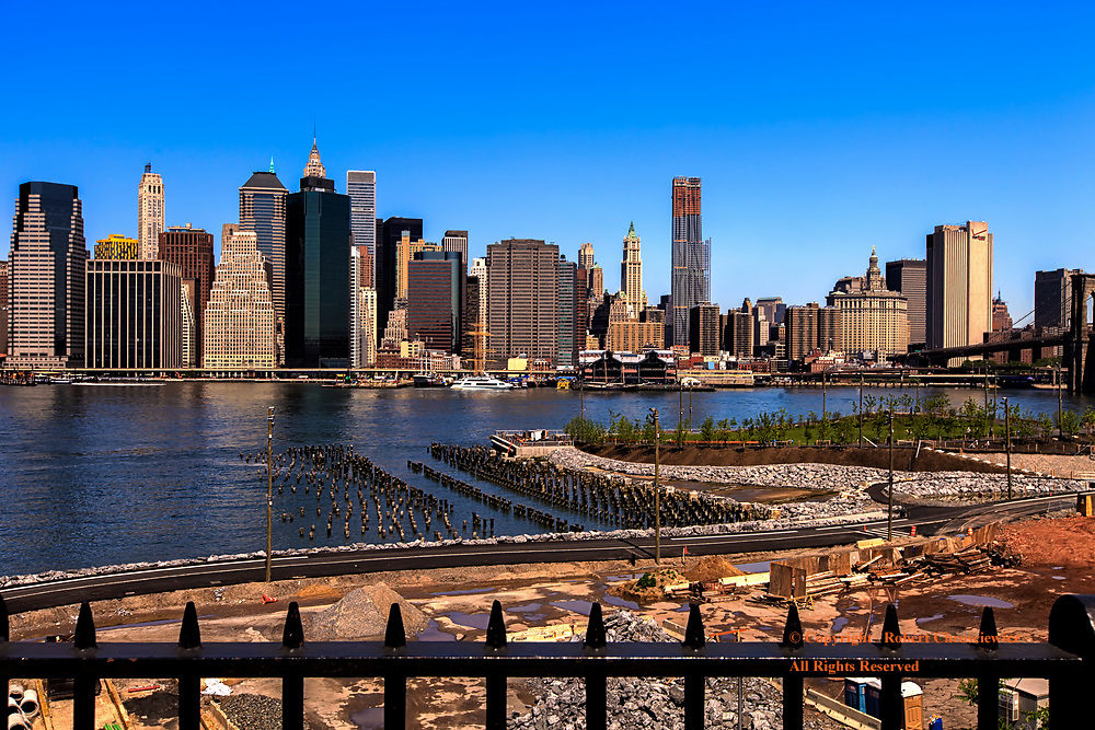 Viewed from Brooklyn, the East River yields this view of sky scrapers  punctuating the blue spring sky over Manhattan, Brooklyn New York, USA.