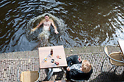 Een man zwemt in de Oudegracht in Utrecht.<br /> <br /> A man is swimming in the canals of Utrecht.