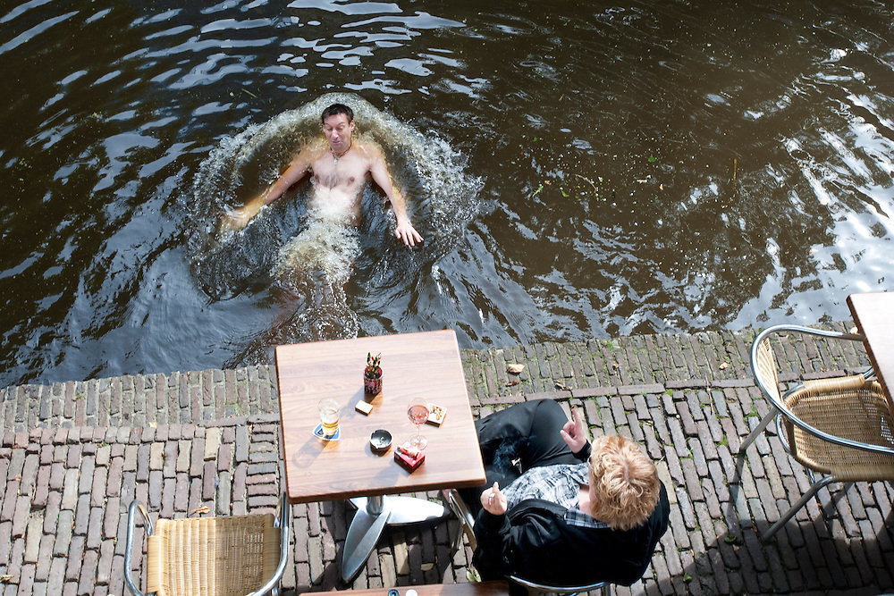 Een man zwemt in de Oudegracht in Utrecht.<br /> <br /> A man is swimming in the canals of Utrecht.