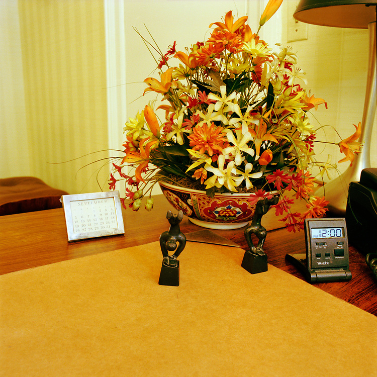 A desk and blotter with two wooden figure sculptures, calendar, small digital clock, a metal lamp, and a large Oriental style planter of colorful flowers.