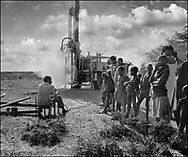 Drilling a water well for the Karamajong by a Lutheran World Federation drilling rig and crew. Karamajong warriors look on. Karamajong of Karamoja, Uganda 1980