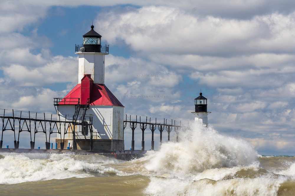 Lake Michigan sends waves crashing into the North Pier lighthouses in Saint Joseph, Michigan on a beautiful cloudy day