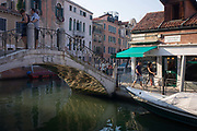 Tourists on the Fondamenta Minotto and on the bridge over the Rio dei Tolentini Canal in Dorsoduro, a district of Venice, Italy. Visitors cross the minor bridge over the canal and others walk along the Fondamenta under a green canopy. Dorsoduro is one of the six sestieri of Venice, in northern Italy, lying to the west of the main tourist area of San Marco.