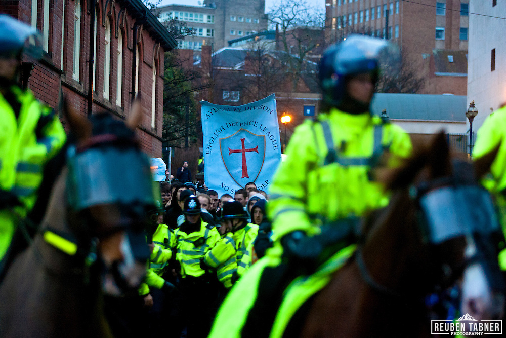 EDL (English Defence League) supporters are marched through Nottingham to the train station, with a heavy police escort in the growing darkness.