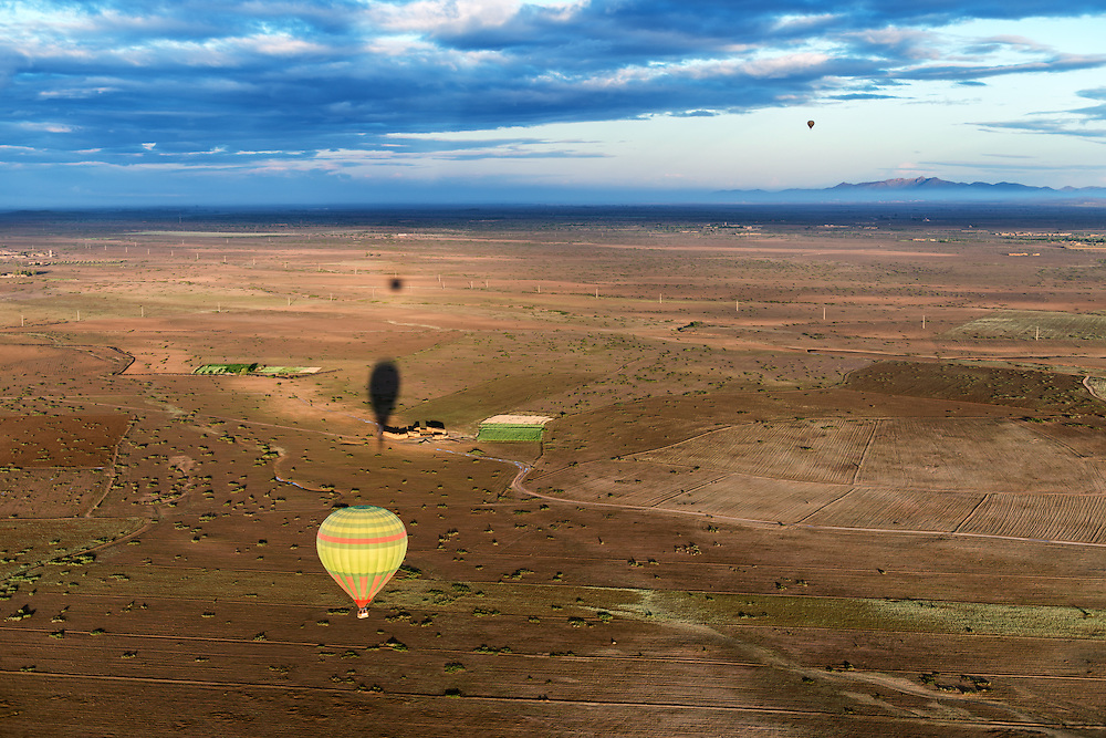 Hot-air balloons with shadows over rural Marrakech, Morocco.