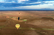 Hot-air balloons with shadows over rural Marrakech, Morocco.