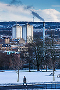 A man walks through the park with two blocks of flats, a smoking chimney and a wind turbine on Glasgow South side taken from Queens Park, Glasgow.