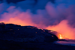 Hot molten lava entering into Pacific Ocean, creating new land and massive steam clouds, Hawaii Volcanoes National Park at night, Kilauea, Big Island, Hawaii, Pacific Ocean..