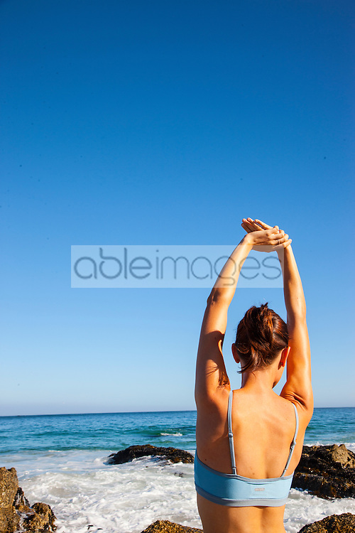 Woman Stretching Arms on Beach, Back View