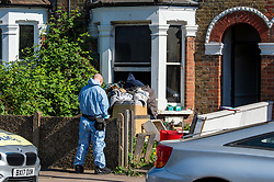 © Licensed to London News Pictures. 25/04/2020. London, UK. A forensic investigator stands outside a property at the scene of a fatal house fire. A man has died in a house fire in Earlsfield, Wandsworth. Firefighters found the man in a ground floor bedroom. He was brought out of the property by fire crews but he died at the scene. London Fire Brigade was called at 07:36 BST and the fire was under control by 08:33 BST. Photo credit: Peter Manning/LNP