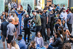 © Licensed to London News Pictures. 23/04/2021. Manchester, UK. Following a day of sunshine , crowds of people fill Cutting Room Square on a Friday night in Ancoats , in the north of Manchester City Centre , as bars and restaurants reopen for outdoor service , following a loosening of Coronavirus controls . Photo credit: Joel Goodman/LNP