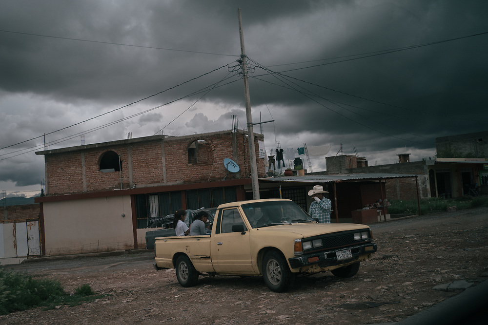A family sits on a car parked by a road in Guadalupe, Zacatecas, Mexico. Hundreds of thousands of people have fled their homes to escape violence; the Mexican Congress is poised to pass the country's first law to help the internally displaced.