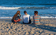 Spring Lake, NJ USA -- October 4, 2017. Friends sit on the beach during a surfing contest  at the end of the season in Spring Lake, NJ.