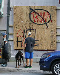 Eric and Nicole Zajkowski, who just fled Hurricane Irma from their home in Coral Springs, Fla., pass by a boarded up store in Savannah, Ga., walking their dog Neeko on Friday, Sept. 8, 2017. The city of Savannah is under mandatory evacuation by Saturday, and the couple said they will have to evacuate a second time. (Photo by Curtis Compton/Atlanta Journal-Constitution/TNS/Sipa USA)