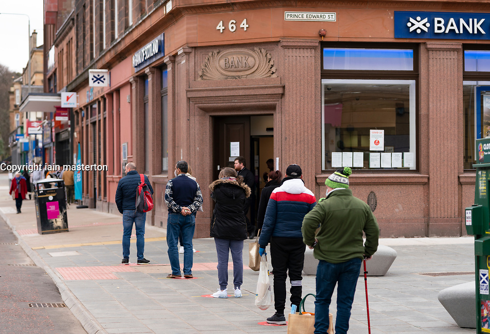 Glasgow, Scotland, UK. 3 April, 2020. Images from the south side of Glasgow at the end of the second week of Coronavirus lockdown. Customers queue to enter the Bank of Scotland branch on Victoria Road, Govanhill. Iain Masterton/Alamy Live News