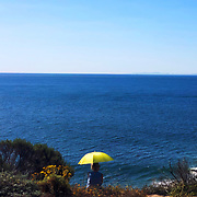 A woman sits under a yellow umbrella on a warm, April morning watching for migrating whales in Malibu, California.
