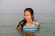 A young Thai woman swimming in the Andaman Sea off Koh Lanta, an island in the south of Thailand.