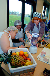 People with learning disabilities learning how to make smoothies at community centre; Bradford Yorkshire UK