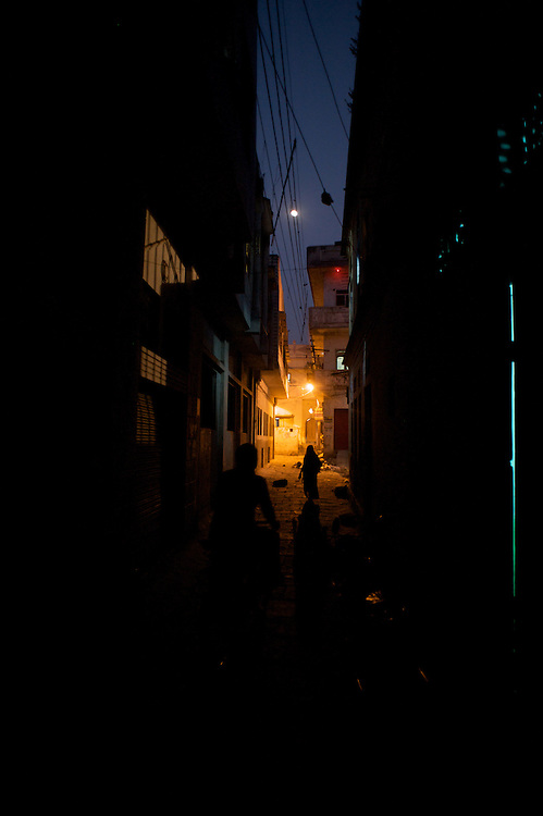 An old woman walks down the street as a young man peddles by on a bicycle in an alleyway in Varanasi, India, beneath a rising moon.