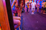 "12 JANUARY 2013 - BANGKOK, THAILAND:  Ladyboy (transgendered) entertainers try to draw customers into the Cockatoo bar in the Soi Cowboy red light district in Bangkok. In Thai, the ladyboys are called kathoey. Many work in the entertainment and night life sectors of the Thai economy. Prostitution in Thailand is illegal, although in practice it is tolerated and partly regulated. Prostitution is practiced openly throughout the country. The number of prostitutes is difficult to determine, estimates vary widely. Since the Vietnam War, Thailand has gained international notoriety among travelers from many countries as a sex tourism destination. One estimate published in 2003 placed the trade at US$ 4.3 billion per year or about three percent of the Thai economy. It has been suggested that at least 10% of tourist dollars may be spent on the sex trade. According to a 2001 report by the World Health Organisation: ""There are between 150,000 and 200,000 sex workers (in Thailand).""    PHOTO BY JACK KURTZ"