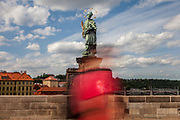 """A woman wearing a face-mask is passing the statue of  """"John of Nepomuk"""" which is an outdoor sculpture, installed in 1683 on the north side of the Charles Bridge in Prague, Czech Republic. The Czech government lowered the security measures and as of Monday 25 May 2020, wearing of protective masks will be mandatory only in the interiors of buildings other than the place of residence and in public transport."""