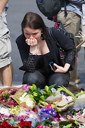 Parliament Square, Westminster, London, June 17th 2016. Following the murder of Jo Cox MP friends and members of the public lay flowers, light candles and leave notes of condolence and love in Parliament Square, opposite the House of Commons. PICTURED: A woman, visibly upset, views the tributes and flowers.