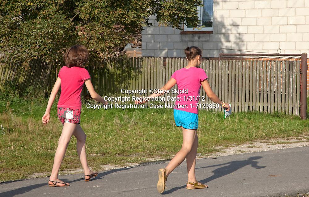 Polish teen girls walking down village street. Mala Wola Central Poland