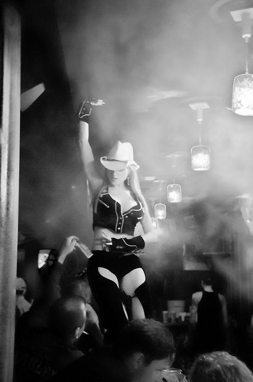 USA, Vereinigte Staaten von Amerika,In Louisiana New Orleans, Eine Frau mit einem Cowboy-Hut und leicht bekleidet tanzt auf dem Tresen einer verrauchten Bar während ihr Männer Dollar-Geldscheine für Ihre Darbietungen zustecken | USA United States of America , Louisiana New Orleans; A woman with a cowboy hat and lightly dressed dances on the counter of a smoky bar while men are putting dollar banknotes on her for her performance