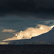 The setting sun casts a glow on mountains in the dramatic Antarctic landscape of Paradise Harbor, Antarctica.