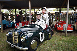 © licensed to London News Pictures. 12/09/2015<br /> Goodwood Revival Weekend, Goodwood, West Sussex. UK.<br /> The Goodwood Revival is the world's largest historic motor racing event. Competitors and enthusiasts dress in period fashions recreating the glorious days of the race circuit.<br /> Pictured 9 year old Henry Alexander and sister Lottie 8 years of age in his Austin J40 peddle car.<br /> <br /> Photo credit : Ian Whittaker/LNP