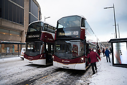 Edinburgh, Scotland, UK. 10 Feb 2021. Big freeze continues in the UK with heavy overnight and morning snow bringing traffic to a standstill on many roads in the city centre. Pic; Lothian Buses bus drivers pass the time waiting for road to clear on Leith Walk.  Iain Masterton/Alamy Live news