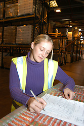 Young trainee working in warehouse; doing stock take; Merseyside UK