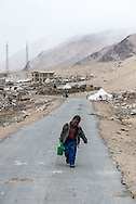 A young Tibetan boy carries water to his families tent in the village of Puga on Ladakh's Changtang.