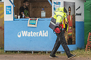 Water Aid, a short downpoor only gives a security guard time to put his jacket over his head - The 2017 Glastonbury Festival, Worthy Farm. Glastonbury, 25 June 2017