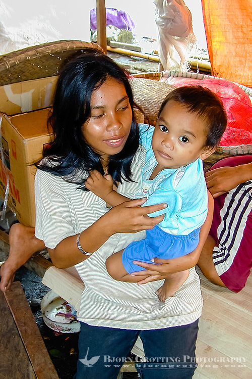 Indonesia, Sulawesi, Manado. The market in Manado harbour. A young mother with her child.