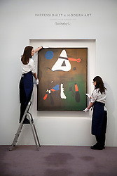 © Licensed to London News Pictures. 01/02/2012. LONDON, UK. Two members of Sotherby's staff adjust 'Peinture' by modernist Joan Miro an auction of Impressionist and Modern Art held on the 8th of February 2012. Created in 1933 the painting is estimated at £7,000,000-10,000,000. Photo credit: Matt Cetti-Roberts/LNP