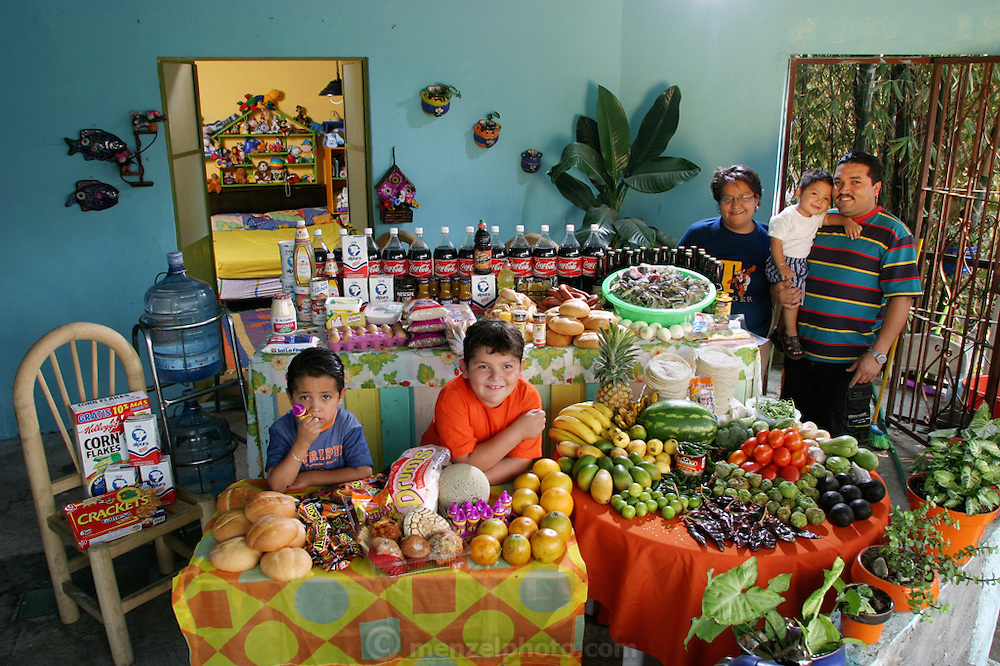 (MODEL RELEASED IMAGE). The Casales family in the open-air living room of their home in Cuernavaca, Mexico, with a week's worth of food. Marco Antonio, and Alma Casales Gutierrez, stand with baby Arath between them. At the table are their older children, Emmanuel, and Bryan. The Casales family is one of the thirty families featured in the book Hungry Planet: What the World Eats (p. 218).