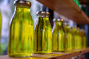 light reflected through bottles of olive oil on a shelf