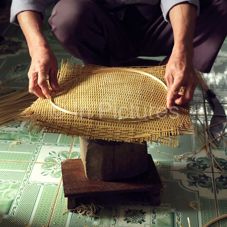 The hands of a man shaping a woven bamboo basket in Tang Tien village, Bac Giang province, Vietnam. With Vietnam's growing population making less land available for farmers to work, families unable to sustain themselves are turning to the creation of various products in rural areas.  These 'craft' villages specialise in a single product or activity, anything from palm leaf hats to incense sticks, or from noodle making to snake-catching. Some of these 'craft' villages date back hundreds of years, whilst others are a more recent response to enable rural farmers to earn much needed extra income.